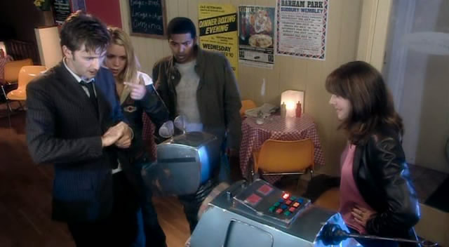 The Doctor has K9 examine the oil while Rose, Mickey and Sarah Jane look on.